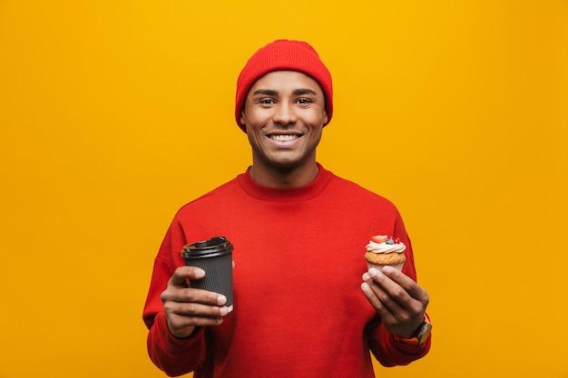 Portret van een aantrekkelijke glimlachende, zelfverzekerde, casual jonge afrikaanse man die over de gele muur staat, met een afhaalkoffiekopje en cupcake