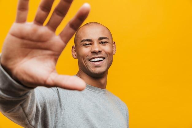 Portret van een aantrekkelijke glimlachende, zelfverzekerde, casual jonge afrikaanse man die over de gele muur staat, met uitgestrekte hand