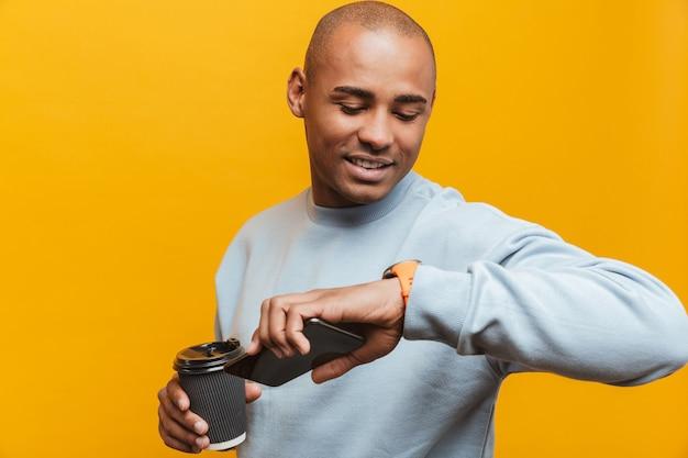 Portret van een aantrekkelijke glimlachende, zelfverzekerde, casual jonge afrikaanse man die over de gele muur staat, mobiele telefoon gebruikt en de tijd controleert