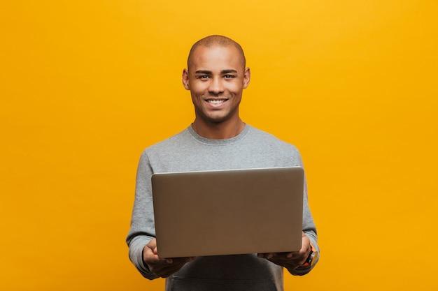 Portret van een aantrekkelijke glimlachende, zelfverzekerde, casual jonge afrikaanse man die over een gele muur staat en een laptop vasthoudt