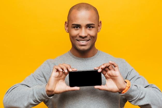 Portret van een aantrekkelijke glimlachende, zelfverzekerde, casual jonge afrikaanse man die over een gele muur staat en een mobiele telefoon met een leeg scherm toont