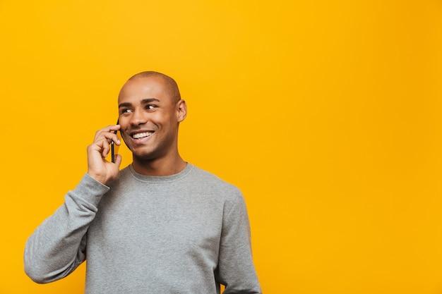 Portret van een aantrekkelijke glimlachende, zelfverzekerde, casual jonge afrikaanse man die over een gele muur staat en op een mobiele telefoon praat