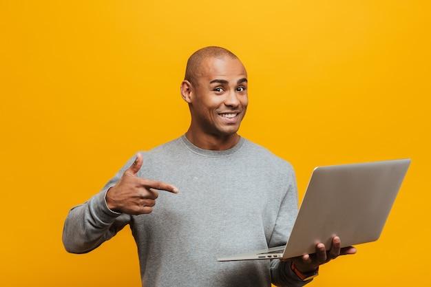 Portret van een aantrekkelijke glimlachende, zelfverzekerde, casual jonge afrikaanse man die over een gele muur staat, wijzend op een laptopcomputer