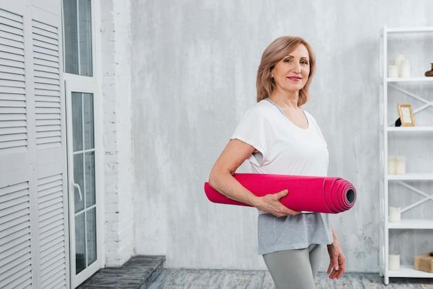 Portret van een aantrekkelijke hogere vrouw die roze thuis mat in hand houdt