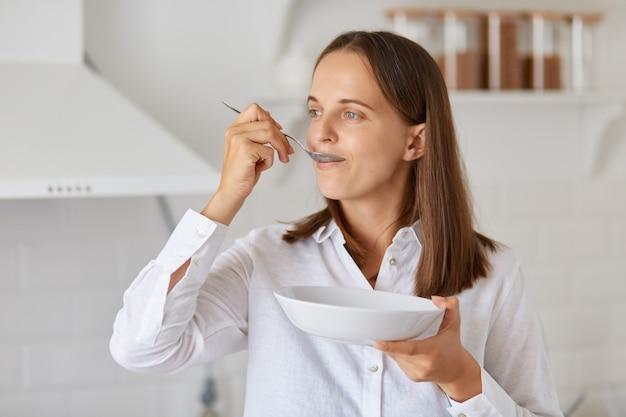 Portret van een aantrekkelijke hongerige vrouw met donker haar in een wit overhemd, wegkijkend, poserend in de keuken, ontbijten, bord en lepel in handen houdend.