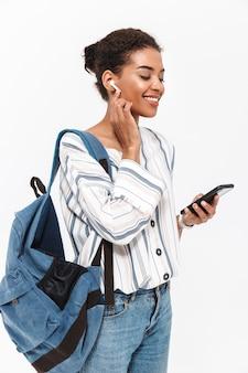 Portret van een aantrekkelijke jonge afrikaanse vrouw met een rugzak die geïsoleerd over een witte muur staat, naar muziek luistert met draadloze oortelefoons, mobiele telefoon vasthoudt