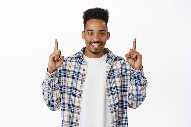 Portret van een aantrekkelijke jonge afro-amerikaanse man die met zijn vingers omhoog wijst, een man die een kortingsadvertentie hieronder laat zien, glimlachend gelukkig op wit.