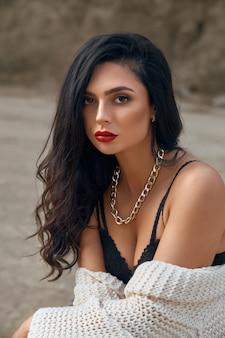 Portret van een aantrekkelijke jonge brunette met een perfecte lichaamsvorm die in een droge zandgroeve zit