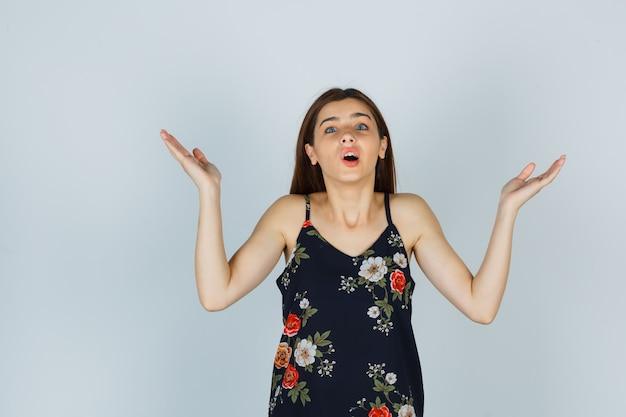 Portret van een aantrekkelijke jonge dame die een hulpeloos gebaar in een blouse toont en een verbaasd vooraanzicht kijkt