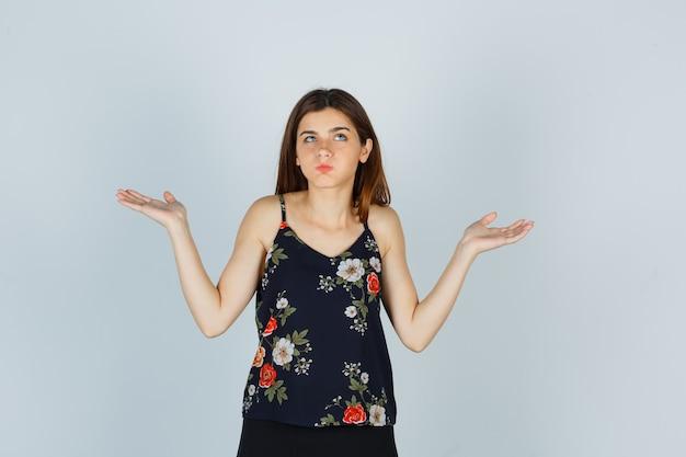 Portret van een aantrekkelijke jonge dame die een hulpeloos gebaar toont, op de wangen blaast in een blouse en er verward vooraanzicht uitziet