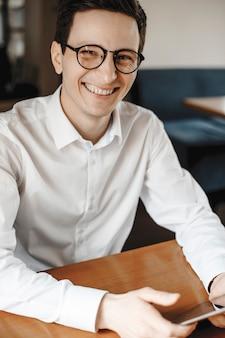 Portret van een aantrekkelijke jonge freelancer die op zijn tablet werkt terwijl hij in een coffeeshop zit die careem lachend bekijkt close-up.