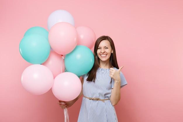 Portret van een aantrekkelijke jonge gelukkige vrouw die een blauwe jurk draagt die kleurrijke luchtballonnen vasthoudt en een duim toont die op een felroze achtergrond wordt geïsoleerd. verjaardagsfeestje, mensen oprechte emoties concept.