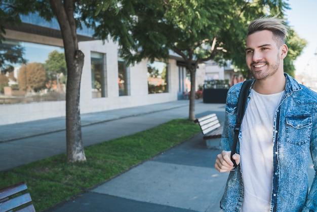 Portret van een aantrekkelijke jonge man die op straat loopt met een rugzak op zijn schouders