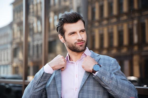 Portret van een aantrekkelijke jonge man die zijn jasje rechtmaakt