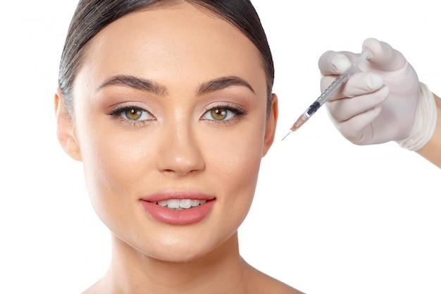 Portret van een aantrekkelijke jonge vrouw die botoxbehandeling ontvangt.