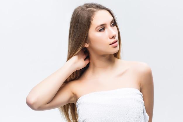 Portret van een aantrekkelijke jonge vrouw die de gladde en gezonde huid van haar gezicht aanraakt en wegkijkt tegen de witte muur