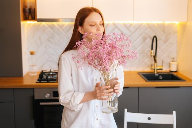 Portret van een aantrekkelijke jonge vrouw die een aromatisch gypsophila-bloemenboeket ruikt in een gezellige woonkamer