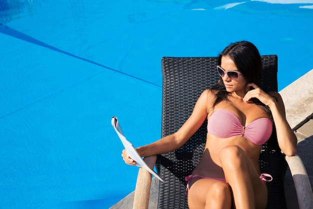 Portret van een aantrekkelijke jonge vrouw die een tijdschrift leest op een ligstoel in de buurt van het zwembad buiten