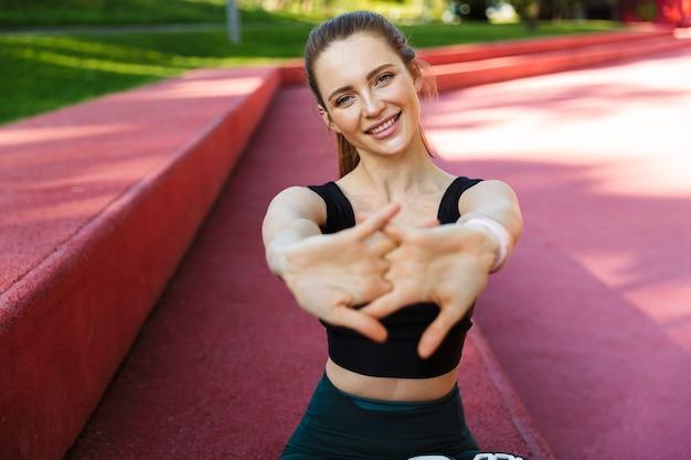 Portret van een aantrekkelijke jonge vrouw die een trainingspak draagt dat glimlacht en naar de camera kijkt terwijl ze op het sportveld zit tijdens de training in het groene park