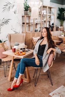Portret van een aantrekkelijke jonge vrouw die in een café zit