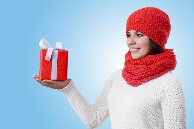 Portret van een aantrekkelijke jonge vrouw die zijwaarts op blauw met warme winterkleren met een cadeautje in haar hand