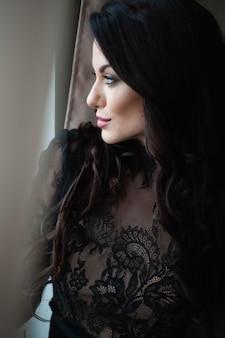Portret van een aantrekkelijke jonge vrouw in strakke zwarte jurk in een luxeappartement.