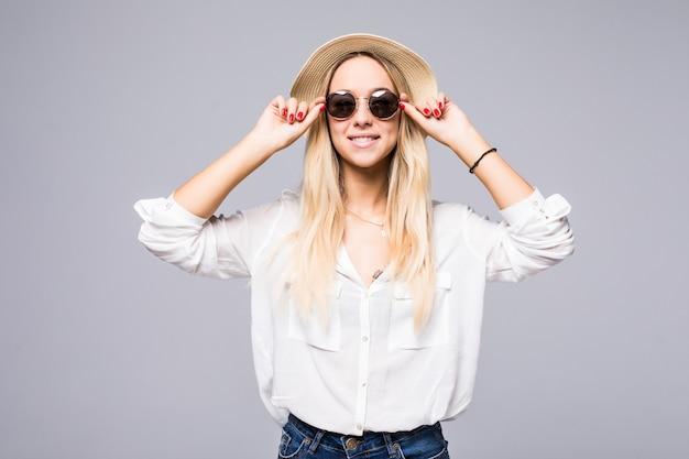 Portret van een aantrekkelijke jonge vrouw in strohoed en zonnebril op grijze muur