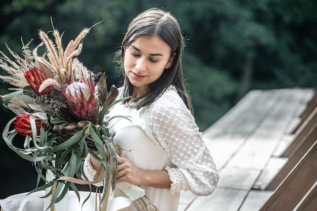 Portret van een aantrekkelijke jonge vrouw met een boeket exotische bloemen, een boeket met protea bloemen.