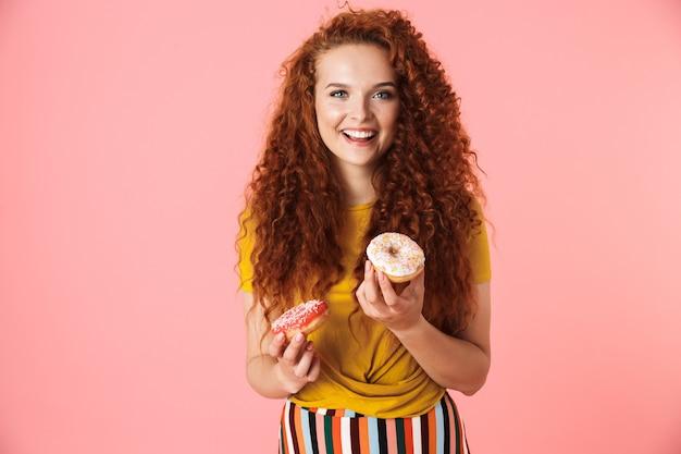 Portret van een aantrekkelijke jonge vrouw met lang krullend rood haar die geïsoleerd staat en donuts eet