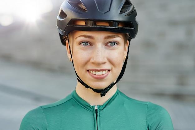 Portret van een aantrekkelijke jonge vrouwelijke fietser met een fietshelm die naar de camera glimlacht terwijl