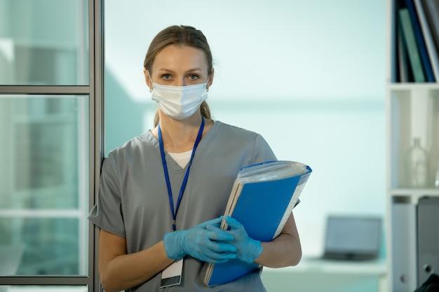 Portret van een aantrekkelijke laboratoriumonderzoeker met een gezichtsmasker en handschoenen met een badge op de nek die op de deur leunt en een map met papieren vasthoudt