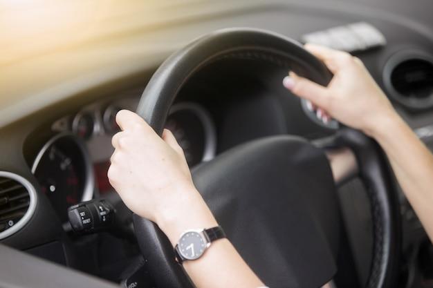 Portret van een aantrekkelijke lachende vrouw die een auto rijdt