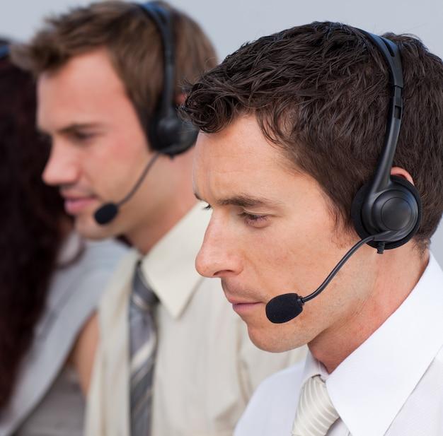 Portret van een aantrekkelijke man aan het werk in een callcenter