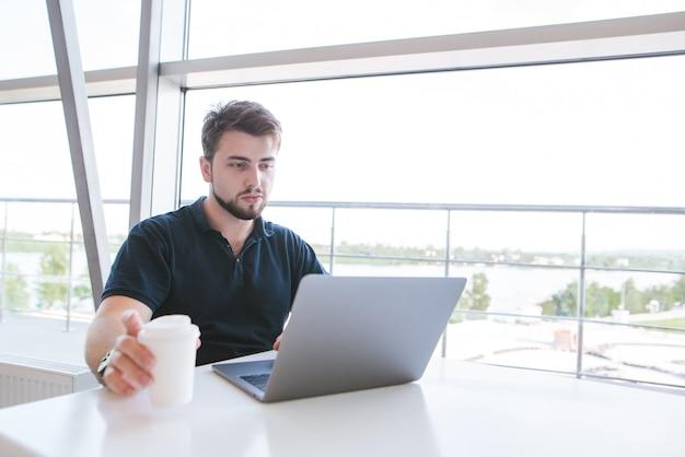 Portret van een aantrekkelijke man met een baard zitten in een lichte cafe in de buurt van het raam en werken op een computer.