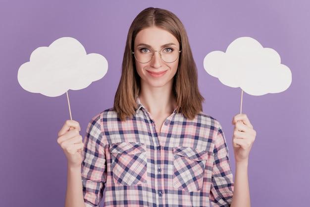 Portret van een aantrekkelijke, mooie dame, een gelukkige positieve glimlach, houdt wolken bubbelweer geïsoleerd op een violette kleurachtergrond