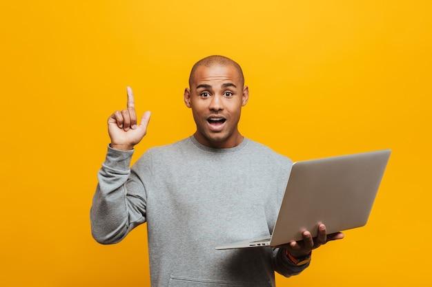 Portret van een aantrekkelijke opgewonden casual jonge afrikaanse man die over een gele muur staat, laptopcomputer vasthoudt, idee
