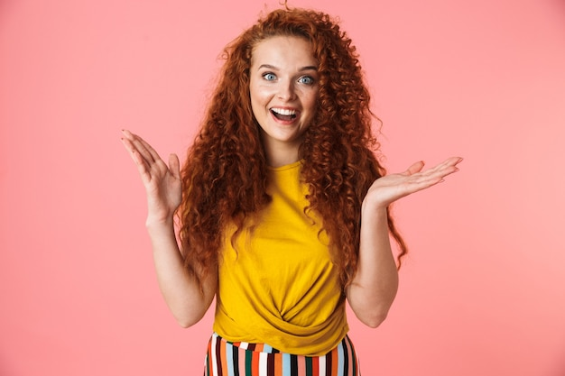 Portret van een aantrekkelijke opgewonden jonge vrouw met lang krullend rood haar dat geïsoleerd staat