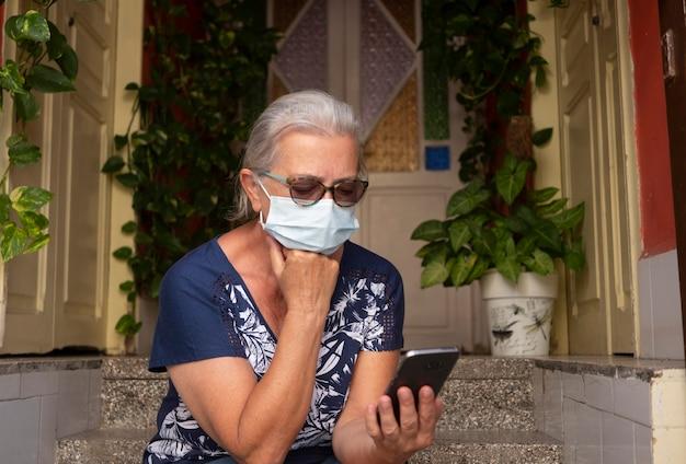 Portret van een aantrekkelijke oudere vrouw met wit haar die een gezichtsmasker draagt als gevolg van het coronavirus met behulp van een smartphone die op de trap zit - concept van gepensioneerde oudere technologie en sociaal