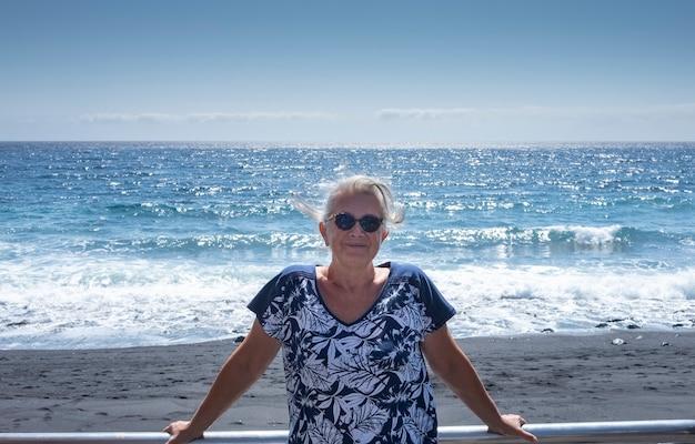 Portret van een aantrekkelijke oudere vrouw met wit haar die lacht onder de zonhorizon boven de zee