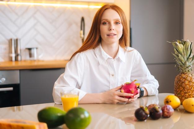 Portret van een aantrekkelijke roodharige jonge vrouw die aan tafel zit met exotisch tropisch fruit in de keuken