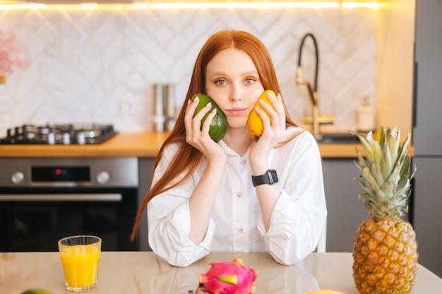 Portret van een aantrekkelijke roodharige jonge vrouw die mango en avocado in handen houdt en aan tafel zit met