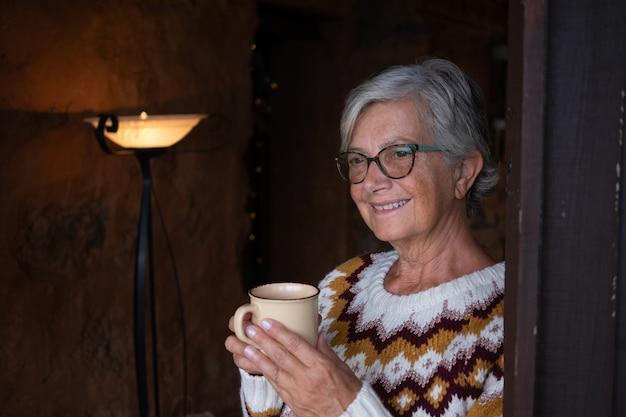 Portret van een aantrekkelijke senior lachende vrouw in huis die een wintertrui draagt en een kopje thee drinkt terwijl ze wegkijkt. ontspannen oudere vrouw grijsharig en brillen