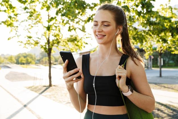 Portret van een aantrekkelijke sportvrouw die een trainingspak draagt dat een smartphone vasthoudt en naar muziek luistert met een koptelefoon tijdens een wandeling door het stadspark