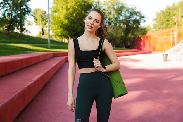 Portret van een aantrekkelijke sportvrouw met een trainingspak en oordoppen met een fitnessmat tijdens een wandeling door het stadspark
