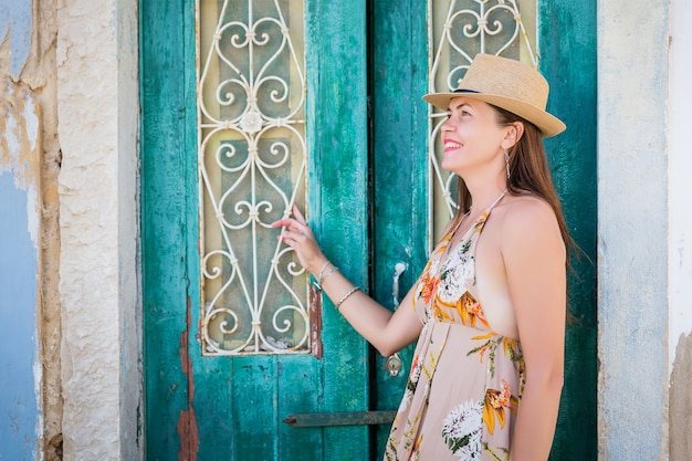 Portret van een aantrekkelijke toeristische vrouw in de oude stad, gekleed in stijlvolle lange jurk, armbanden en strooien hoed