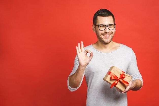 Portret van een aantrekkelijke toevallige mens die huidige doos geeft en camera bekijkt die over rode achtergrond wordt geïsoleerd