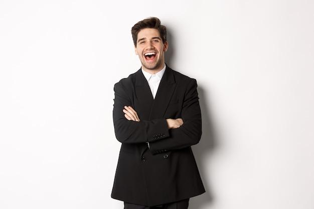 Portret van een aantrekkelijke volwassen man in pak die lacht en er gelukkig uitziet, in pak staat met de handen over de borst gekruist, poserend tegen een witte achtergrond