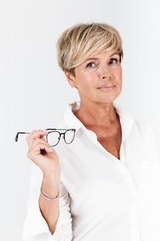 Portret van een aantrekkelijke volwassen vrouw die een bril vasthoudt en naar een camera kijkt die over een witte muur in de studio wordt geïsoleerd