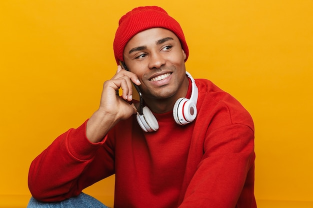 Portret van een aantrekkelijke, vrolijke, informele jonge afrikaanse man die op een vloer over een gele muur zit en op een mobiele telefoon praat