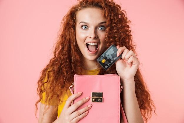 Portret van een aantrekkelijke, vrolijke jonge vrouw met lang krullend rood haar dat geïsoleerd staat en een creditcard in haar tas stopt